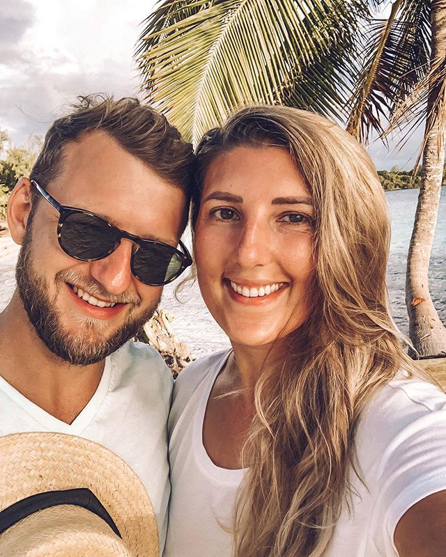 a couple smiling for a selfie in a tropical setting