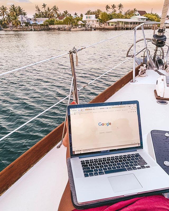 a laptop open to the Google homepage sitting on the cockpit of a sailboat