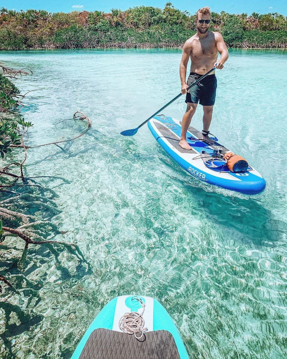 a man paddle boards in shallow, clear water