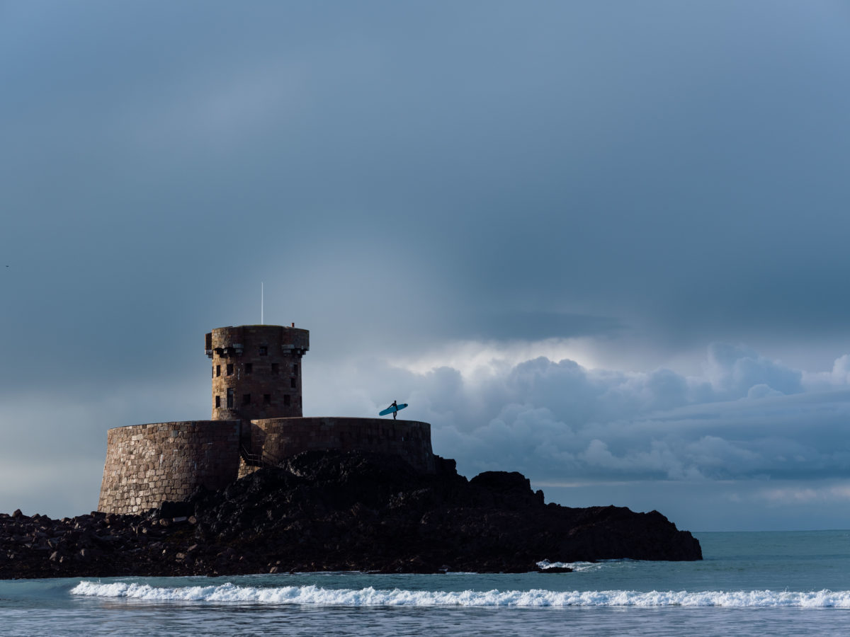 a surfer standing on top of the castle in the ocean