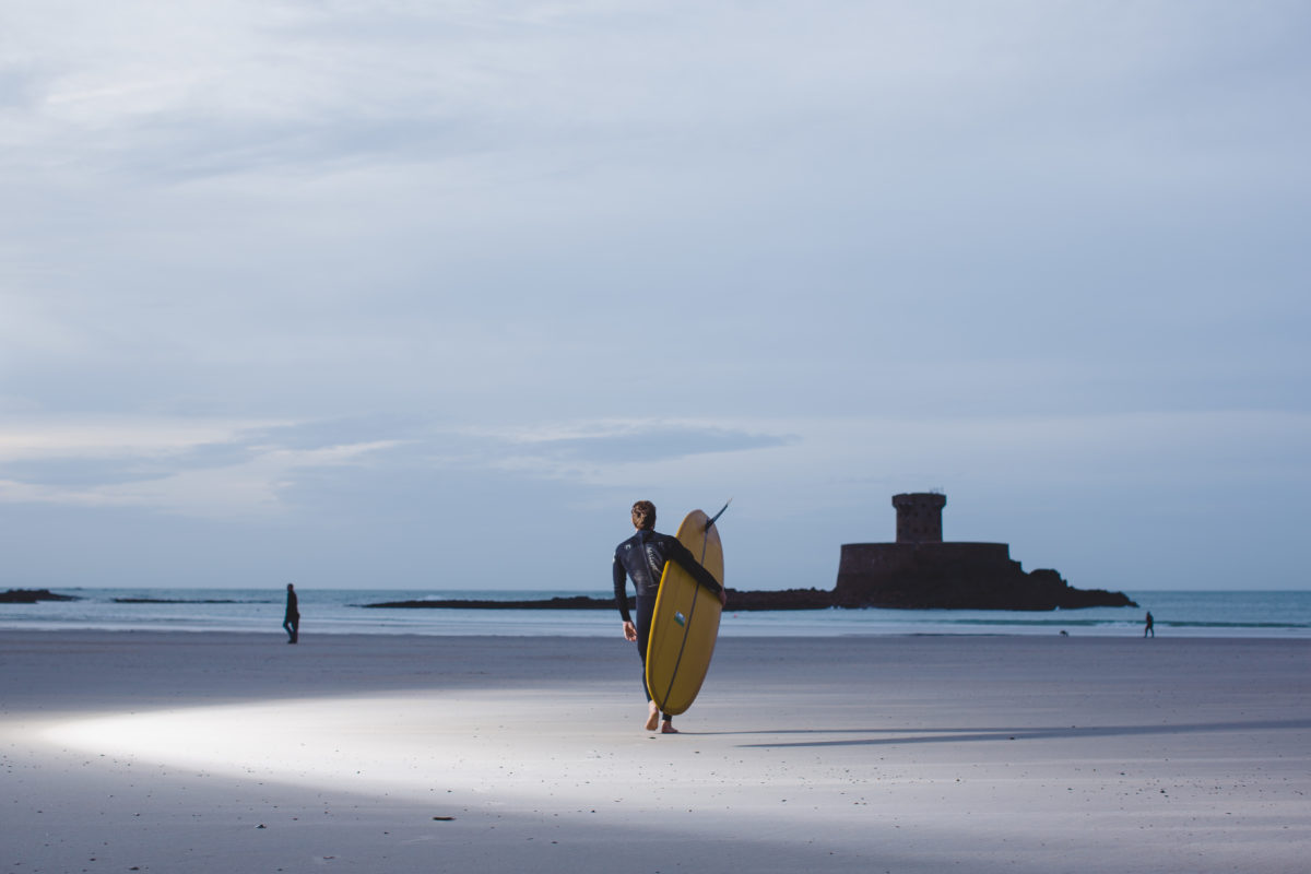 a surfer walking towards the ocean with a castle in the distance