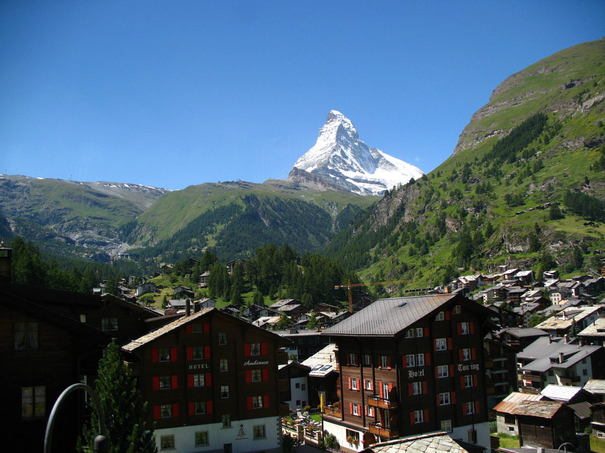 a snowcapped mountain overlooking a quaint village in a valley