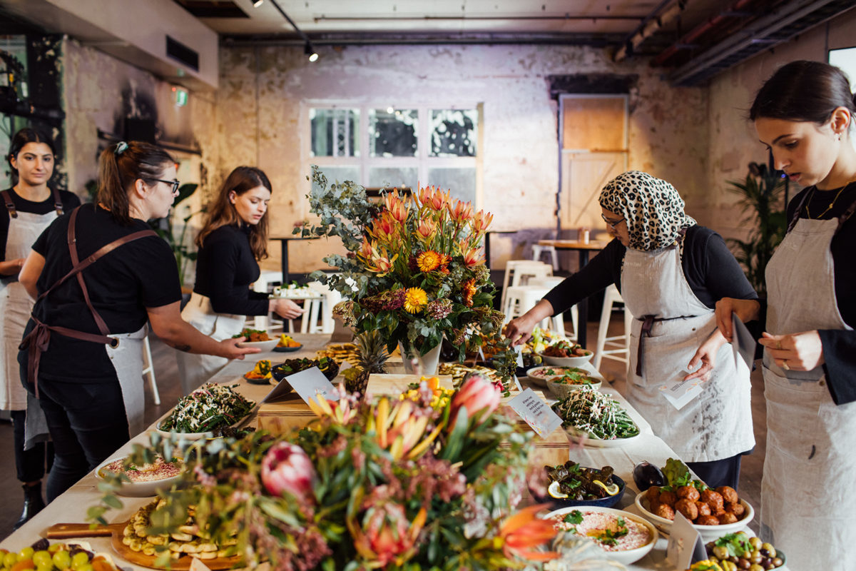 people preparing a dinner on a table full of flowers