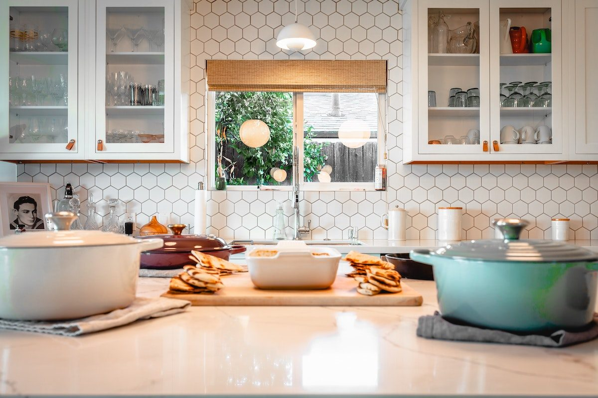 white kitchen with dutch ovens and bread on the counter