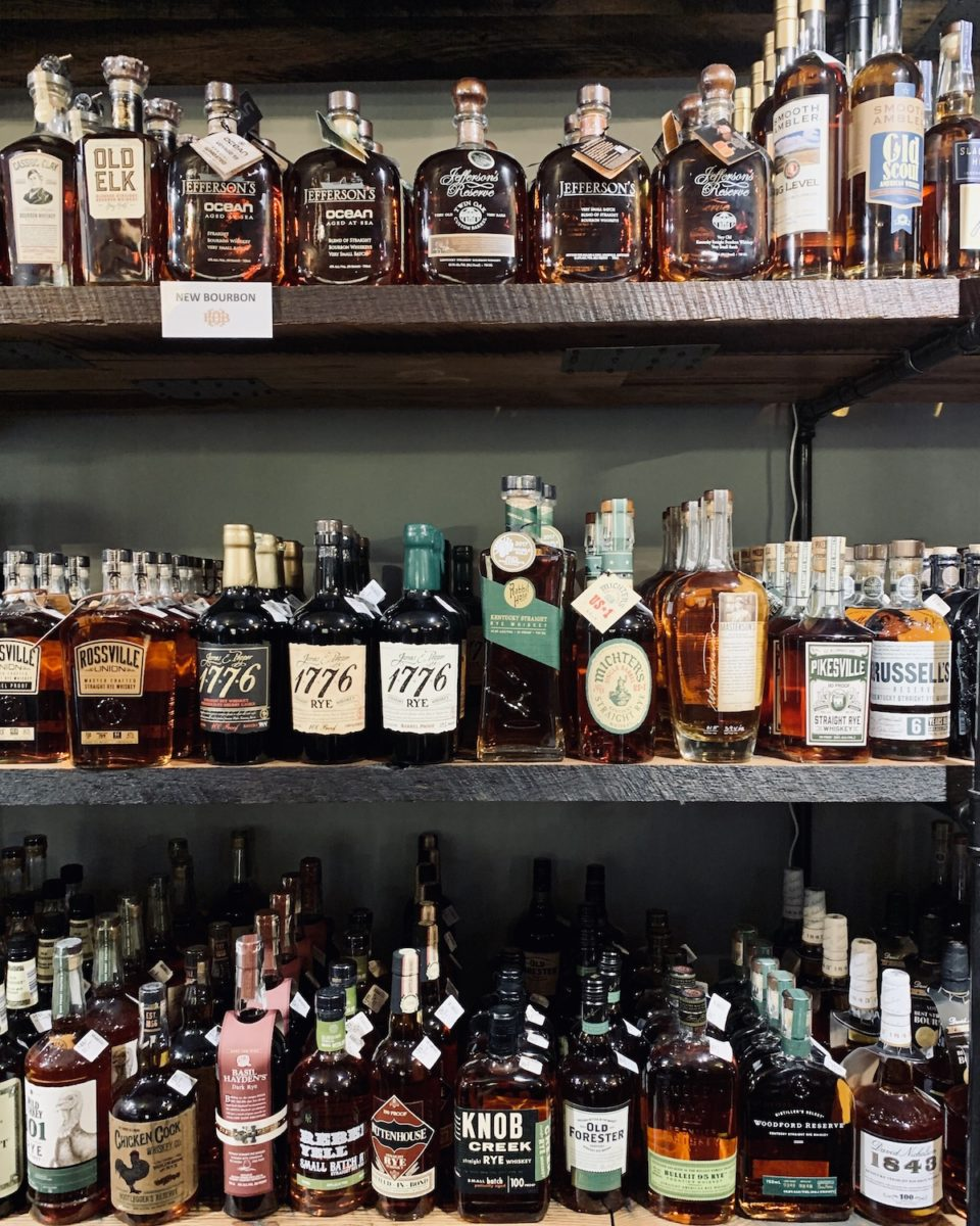three shelves with rows and rows of various bourbon bottles