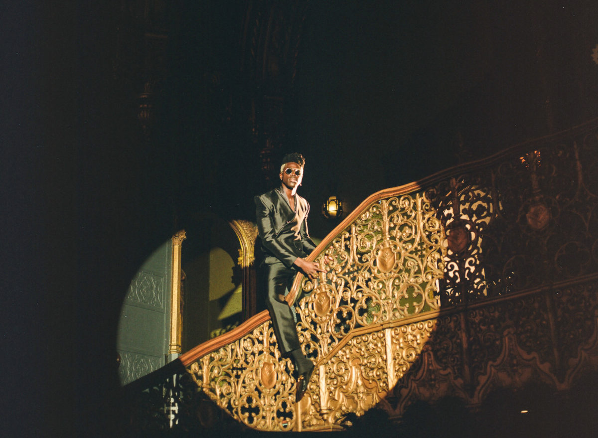 a man in a suit poses on a staircase
