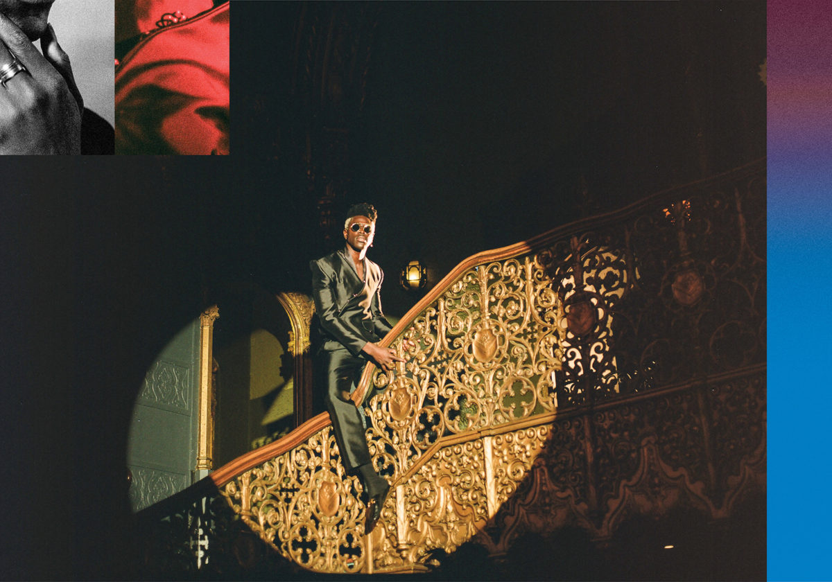 Moses Sumney straddling the railing of an ornate staircase with a circular spotlight shining on him
