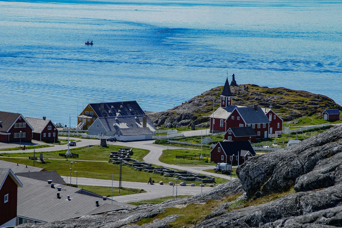 a road through an arctic town leading to the sea