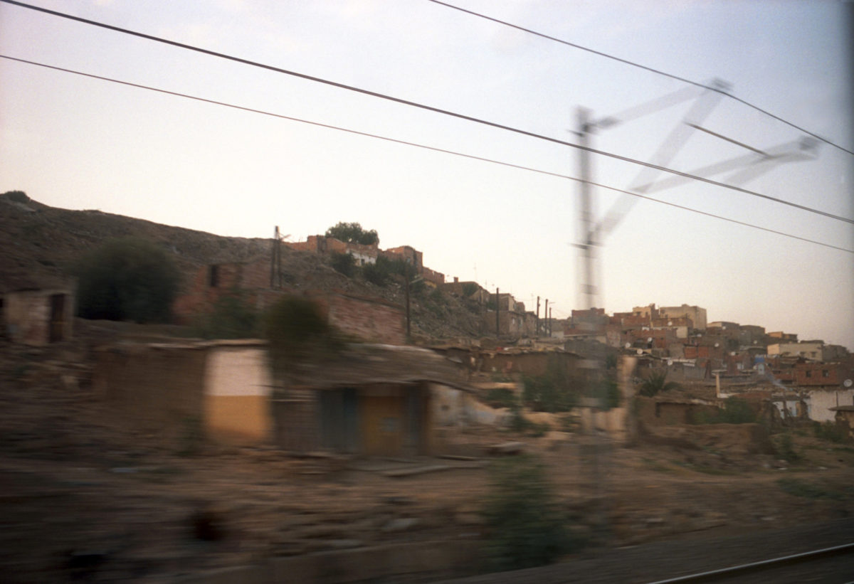 A Moroccan village whisks by from the view of a moving train.