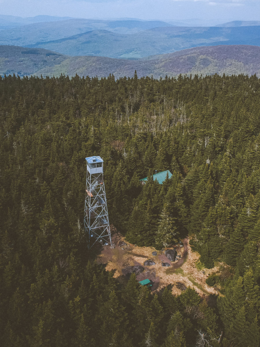 a tower in the middle of the woods surrounded by mountains