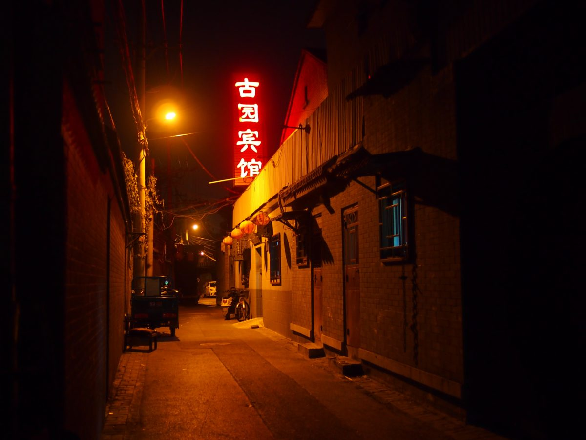 A quiet alleyway with neon sign of red Chinese letters