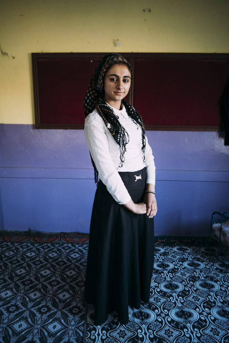 portrait of a Turkish woman wearing a long black skirt and white long-sleeved shirt