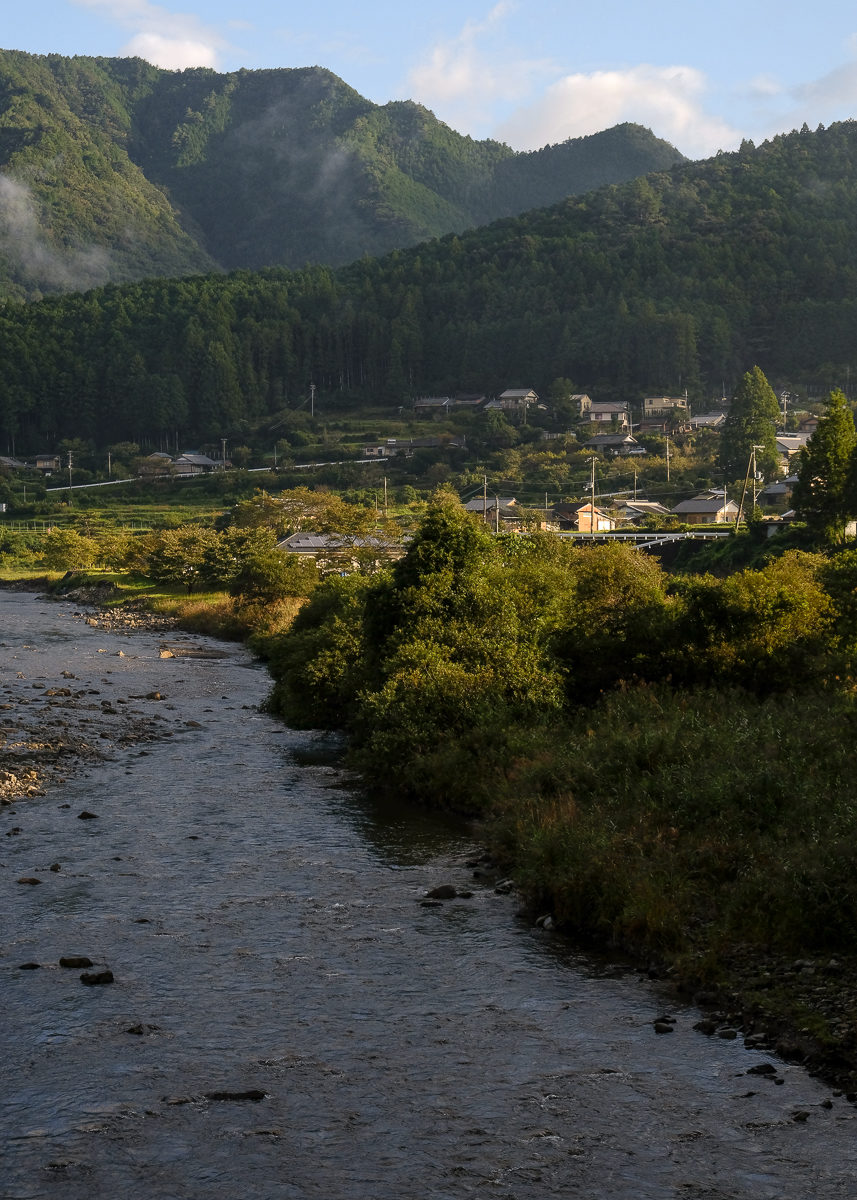 A wide river passes by a small village in the mountains