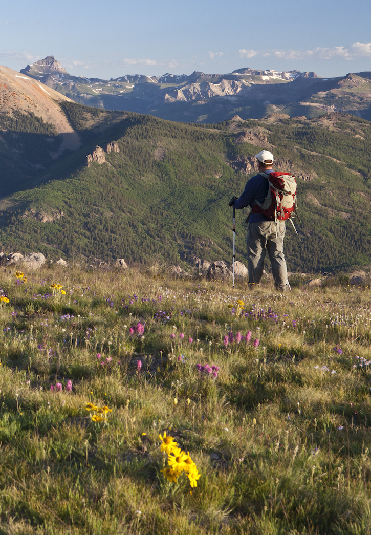 a man hiking on a grassy mountain