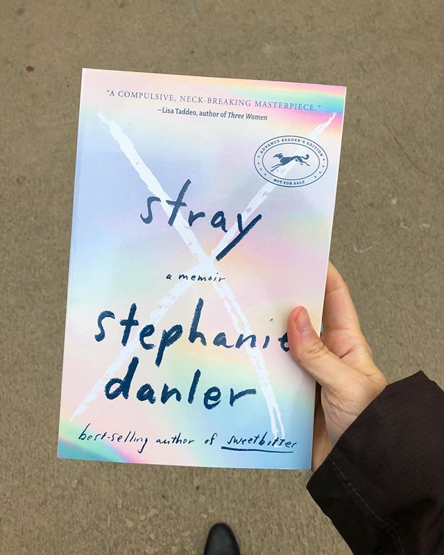 a hand holds the galley of Stephanie Danler's memoir called Stray. The cover is a mix of light, iridescent rainbow gradients with black handwritten text.