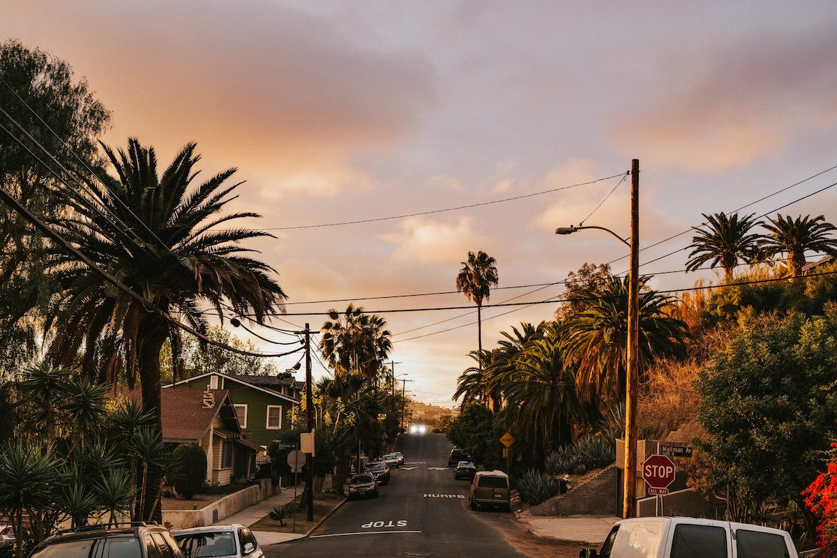 side street in Silverlake neighborhood of LA at dusk. Streets are lined with palm trees. One story houses.
