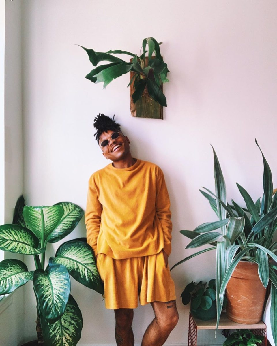 Person in a yellow outfit standing against a wall filled with plants, smiling.
