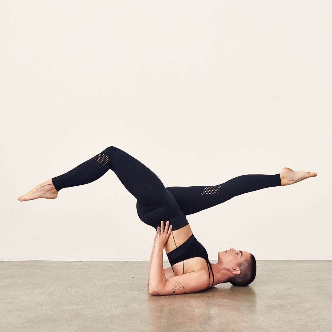 person doing a yoga post on the ground against a white wall