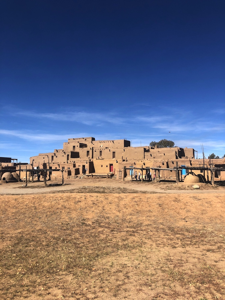 vista of pueblo buildings in the desert on a clear blue day