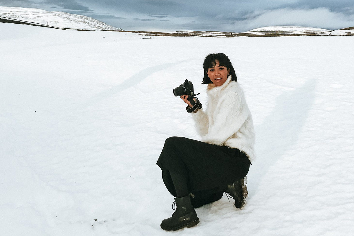 a woman kneeling with a camera in snow