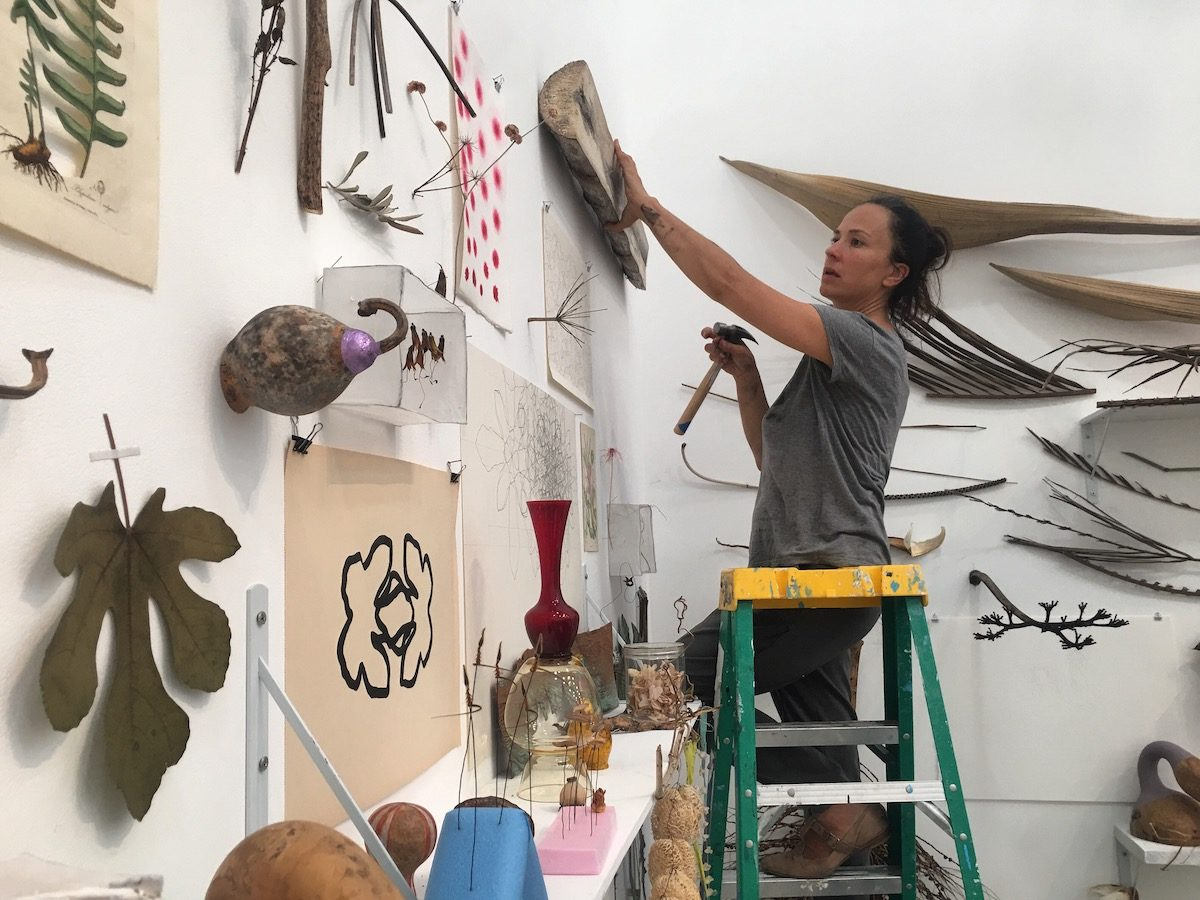 woman on a ladder installing artwork to a white wall