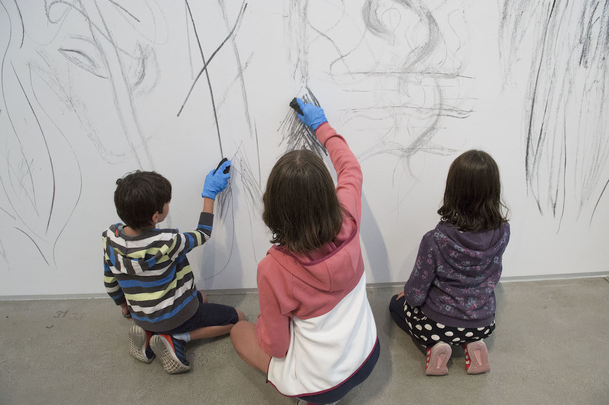 kids drawing with burnt twigs on a white wall