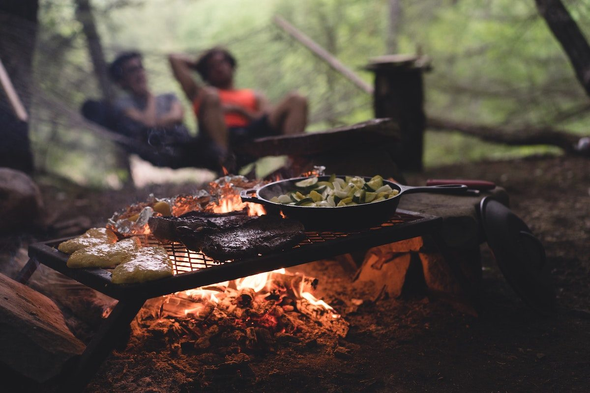 two people cooking food over campfire