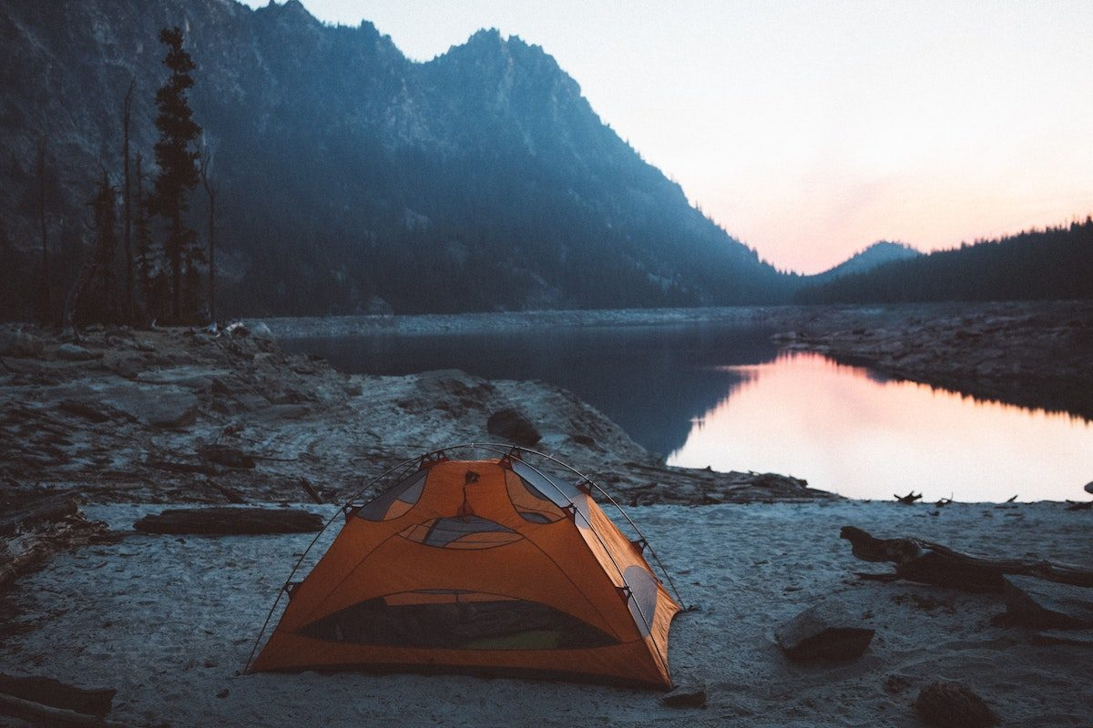 a tent pitched by a lake and mountains