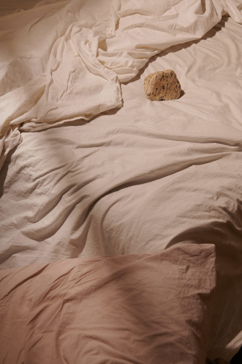 soft shadows criss-cross messy mauve sheets on a bed with a pink rock paper weight in the top right corner of the bed