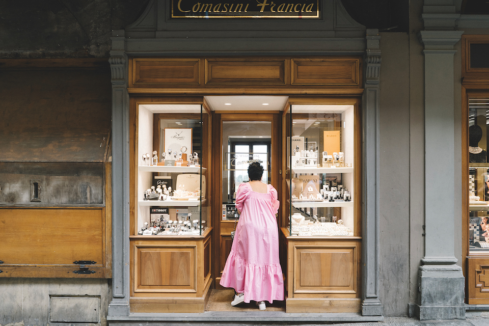 a woman in a dress gazing through a shop window