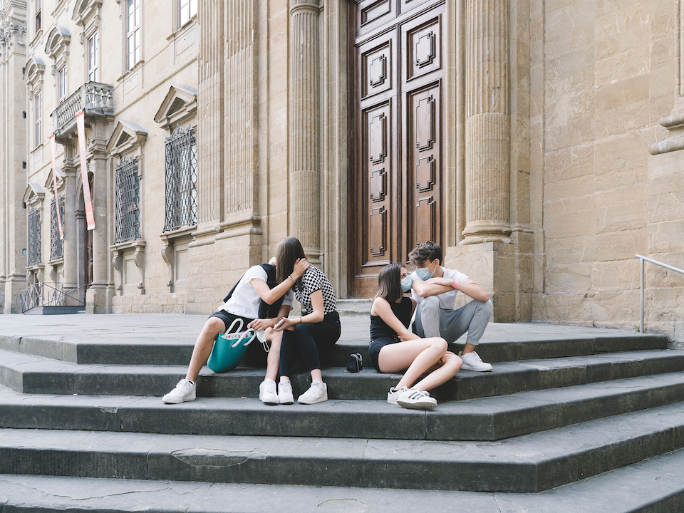two couples talking and kissing on the steps of a building