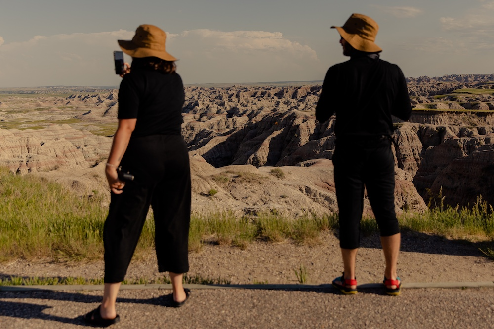 a man and a woman taking photos of Badlands