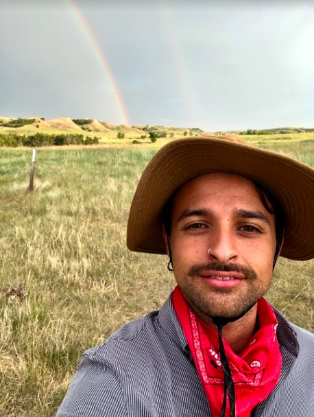 man in a hat taking a selfie in front of a pasture with a rainbow in the background