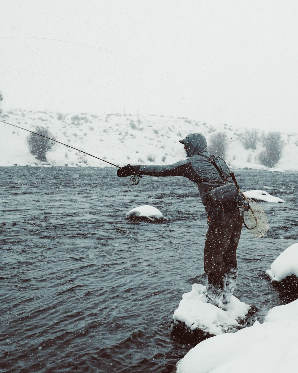 man standing on an icy rock fly fishing into a river in a snow storm. the land surrounding the water is covered in snow.