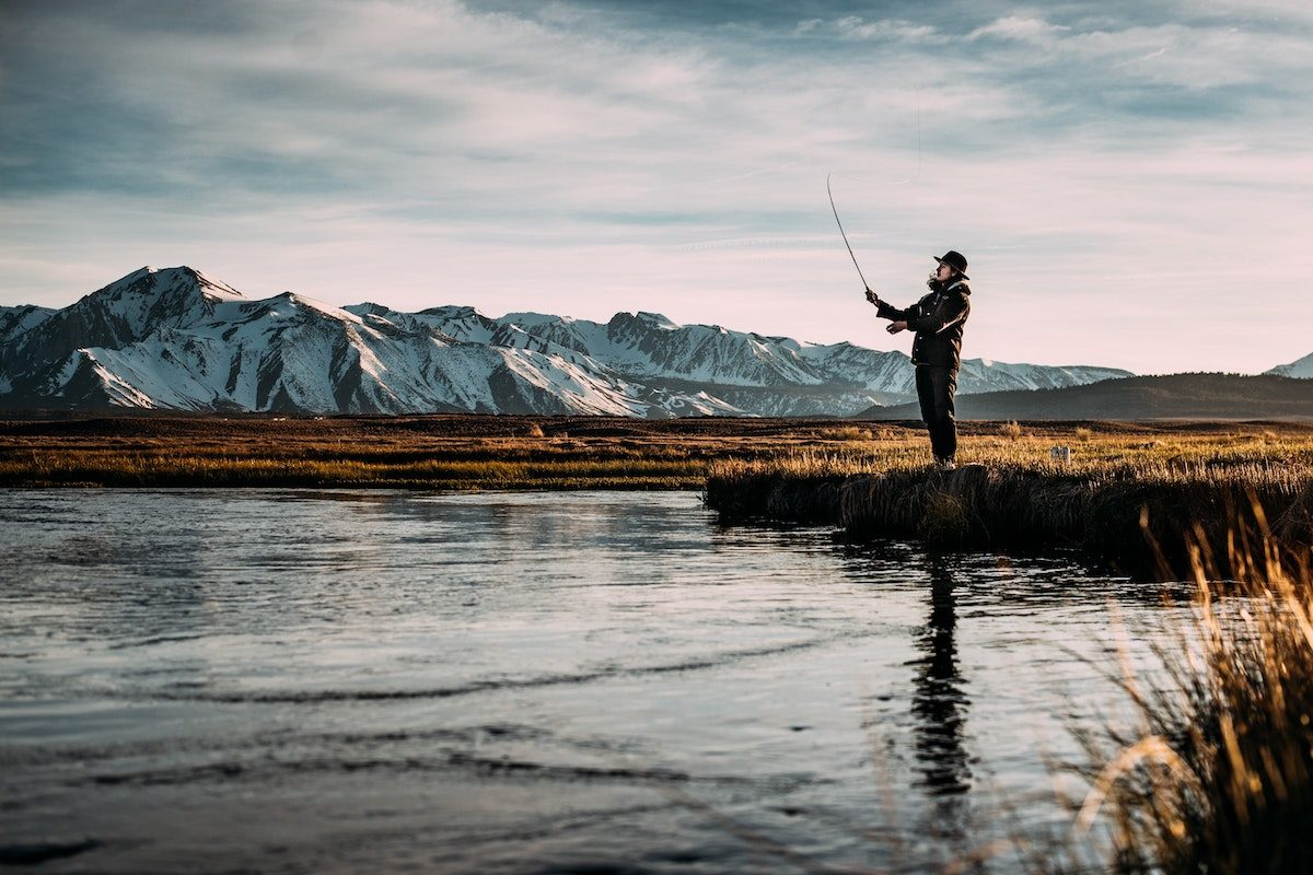 man standing at the edge of a shallow river fly fishing with snow-capped mountains in the background