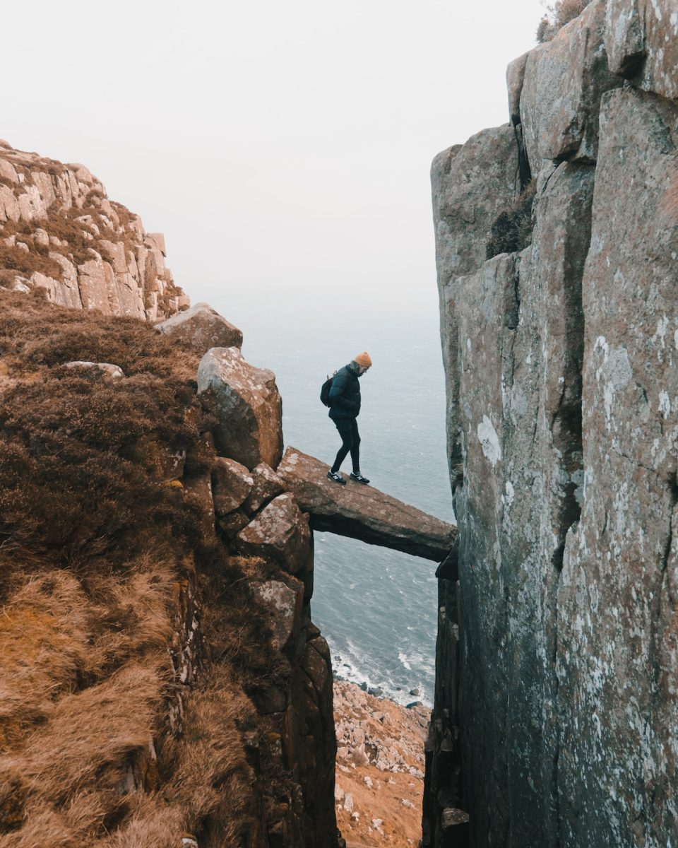 man hikes on a narrow rock stymied between two cliffs