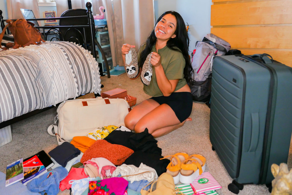 a woman smiles in front of unpacked suitcases