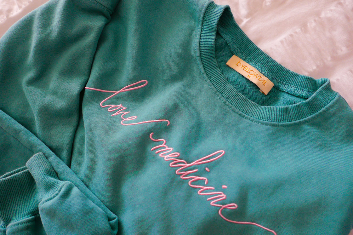 "a sweatshirt with ""love medicine"" embroidered"