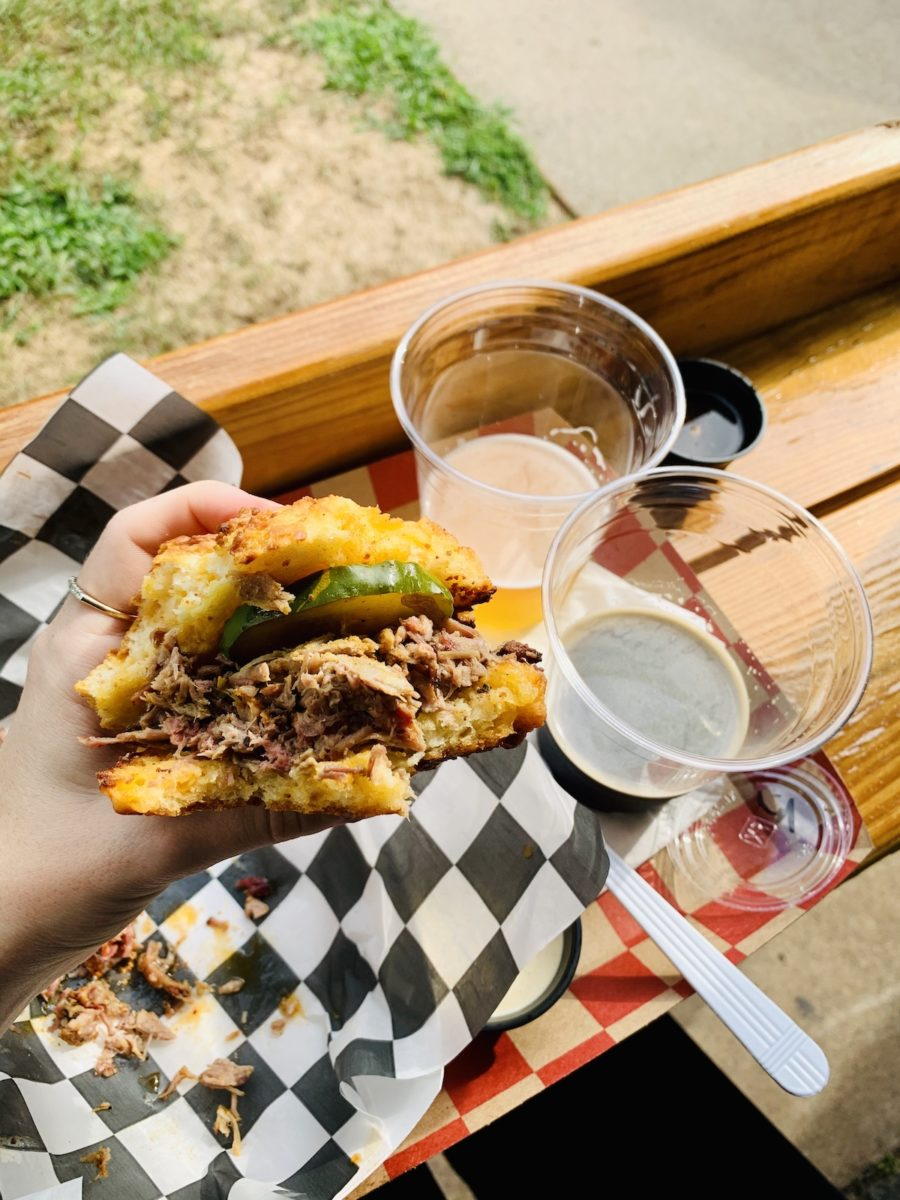 hand holding bbq sandwich over beer