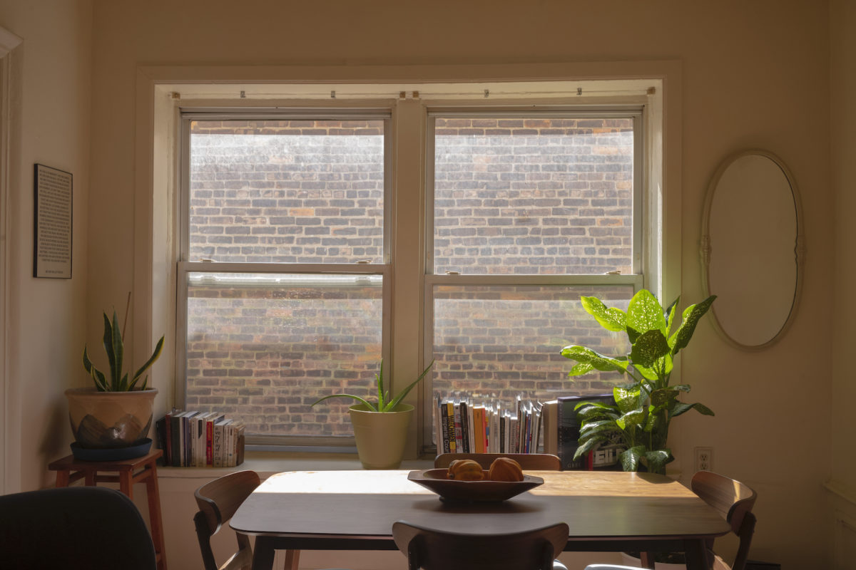 an apartment window with a table and books