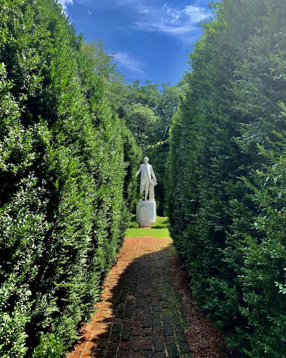 white statue of a man surrounded by topiary
