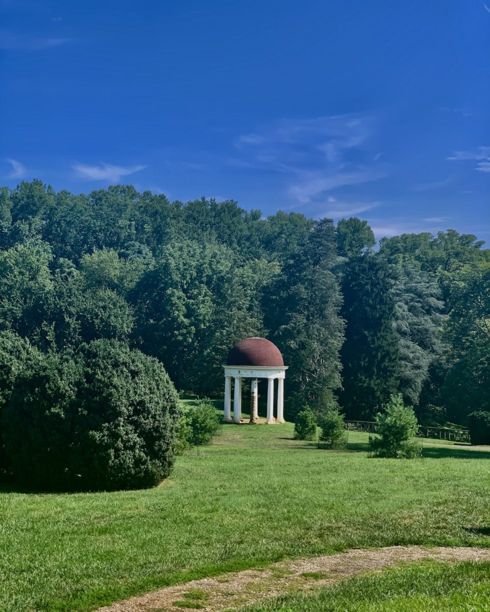 neoclassical gazebo surrounded by trees and green lawn