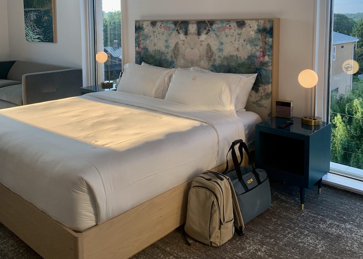 a backpack and weekender bag next to a hotel bed