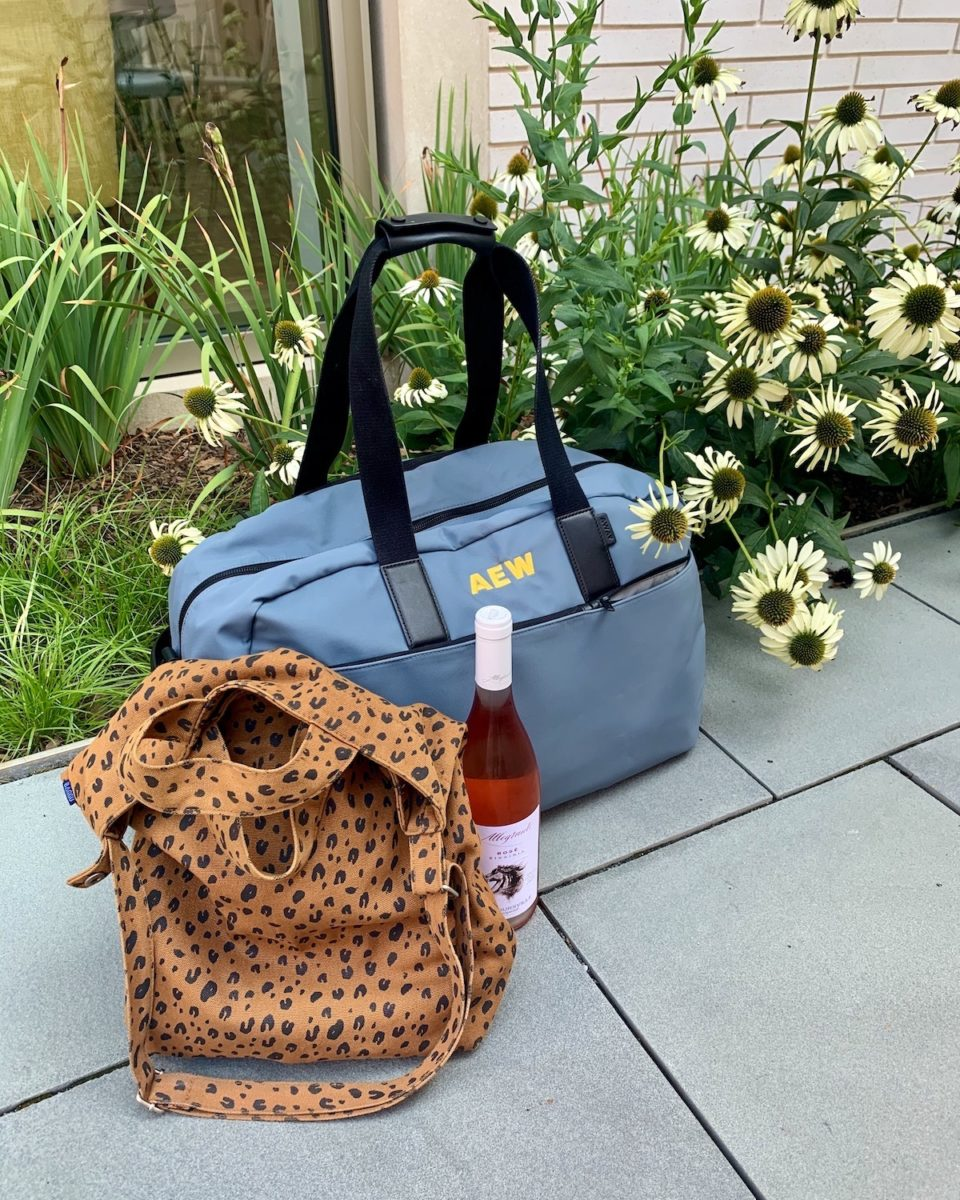 a weekender bag with a tote and wine bottle next to side walk flowers