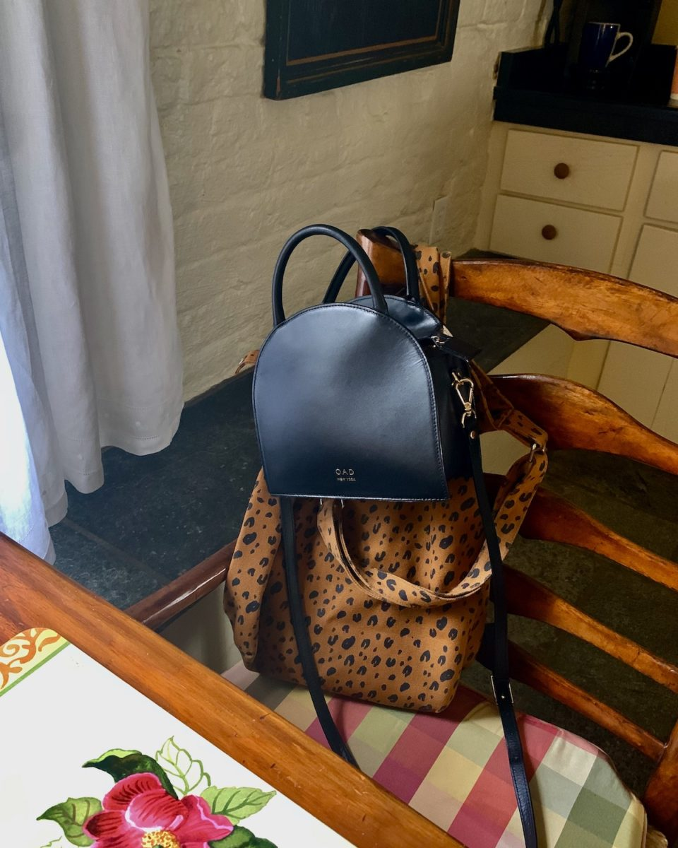 a tote and a black crossbody bag on a chair