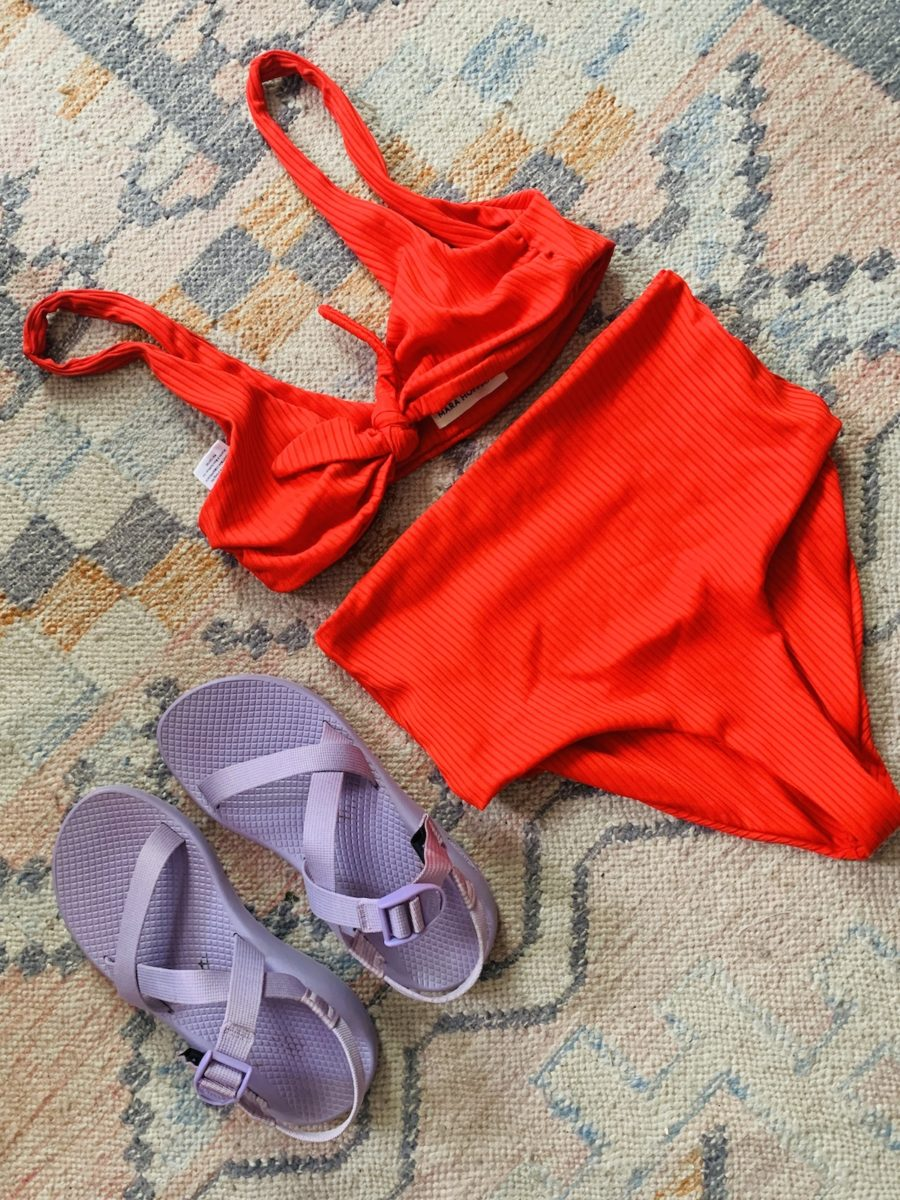 a pair of lavender sandals next to a red bikini on a rug
