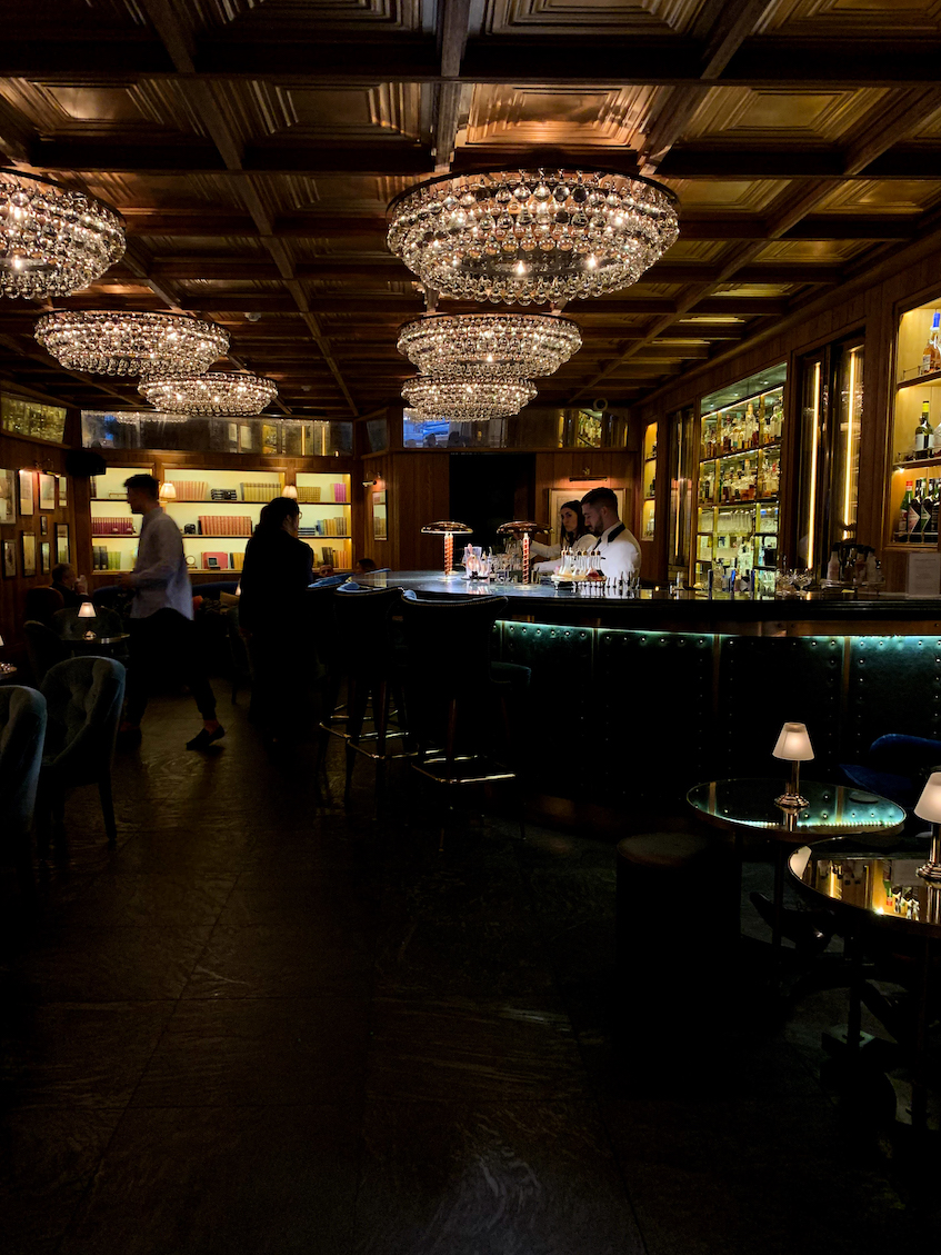 a dimly lit bar with chandeliers