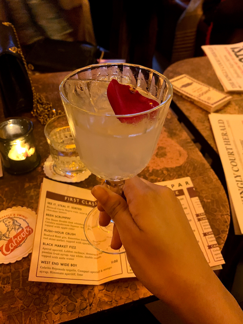 a cocktail with a flower petal in it