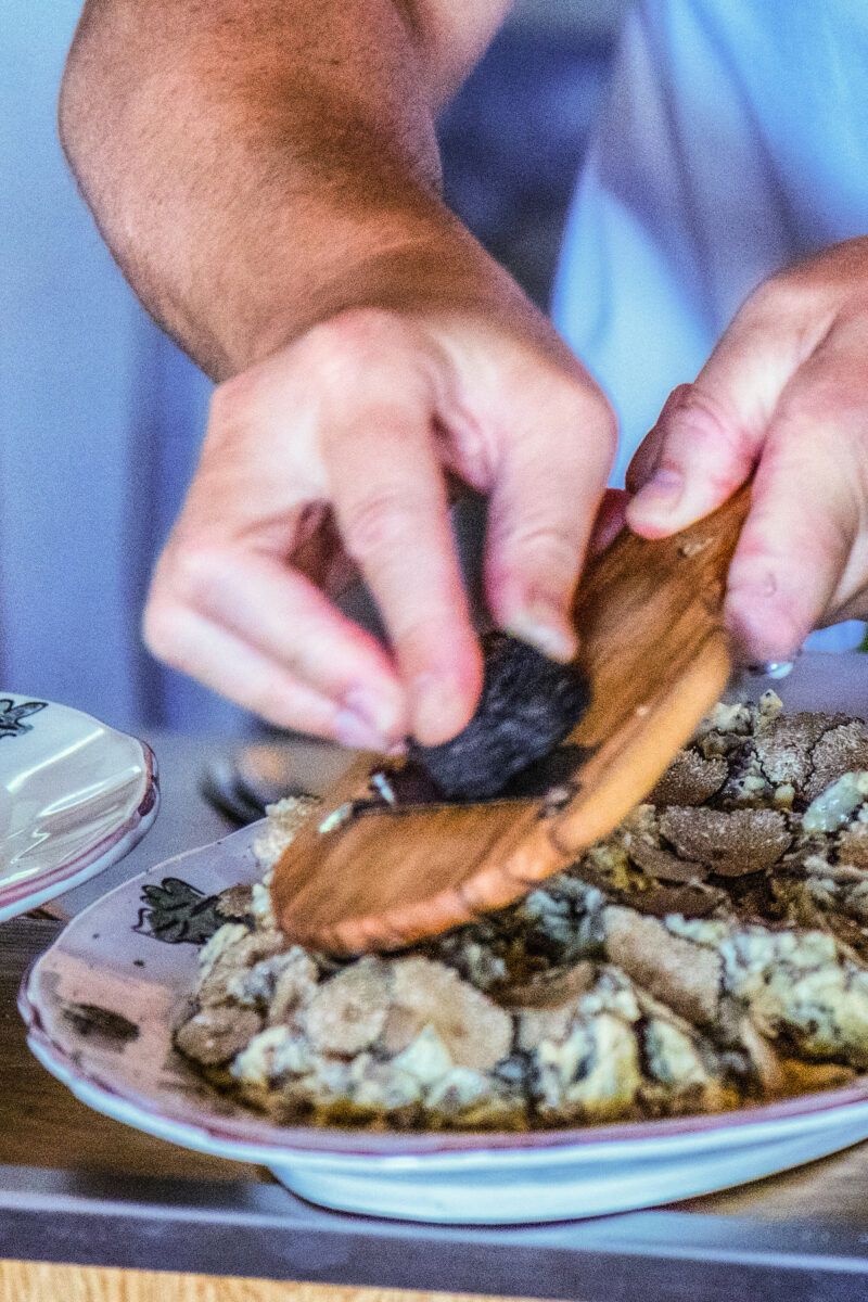 chef shaving truffles over a pasta dish