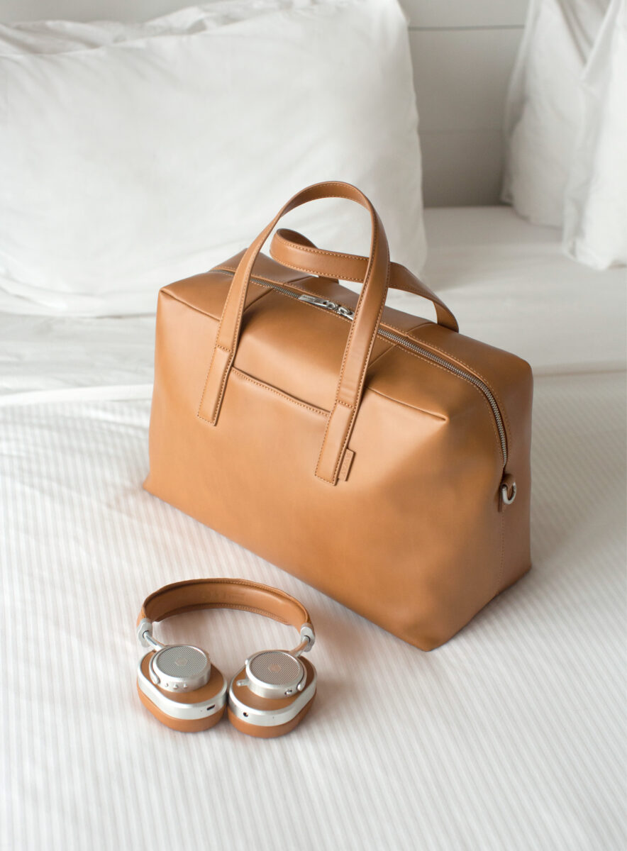 headphones and a suitcase on a bed